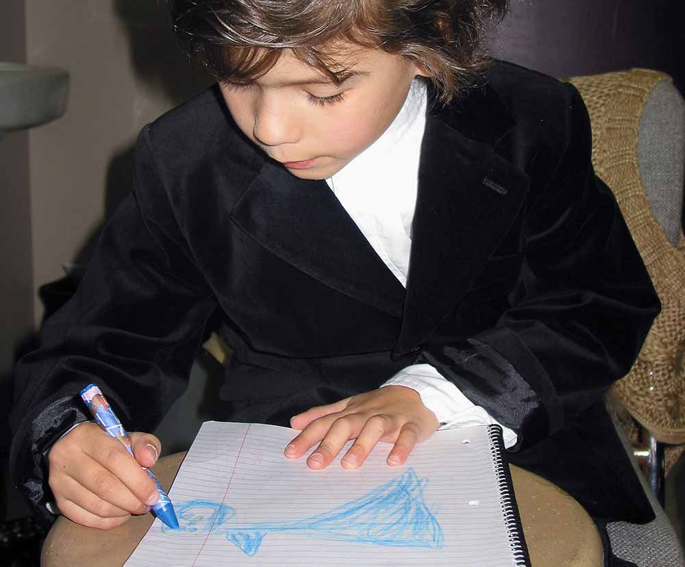 Young designer drawing on some paper with a blue crayon.
